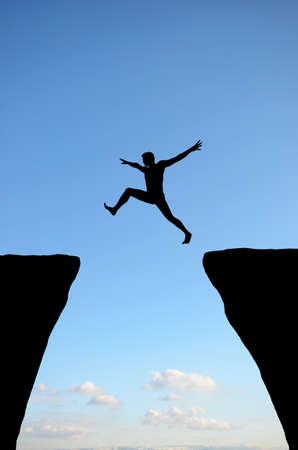 a man jumps from one rock to another