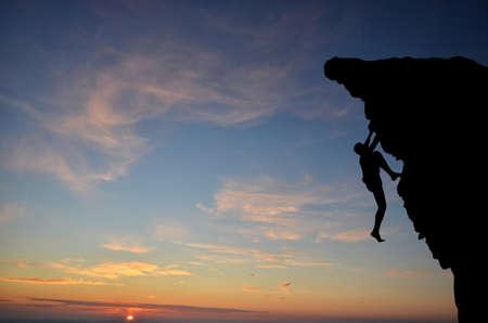 klimmer: silhouet van een persoon zonder verzekering klimt de rots op de achtergrond van de ondergaande zon Stockfoto