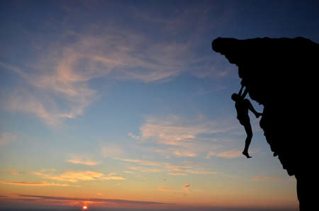 free climber: silhouette of a person without insurance climbs the rock in the background of the sunset