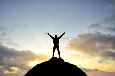 Mann auf dem Gipfel des Berges erreicht für die Sonne