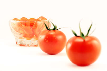 whole and sliced tomatoes in a dish on a white background photo