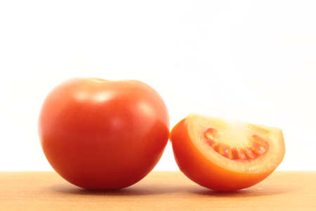 one half of a tomato and tomato are on board on a white background Stock Photo - 12656058