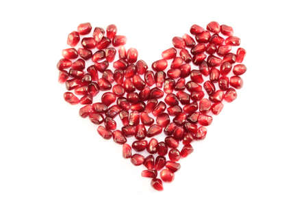pomegranate fruit in the shape of hearts on a white background photo