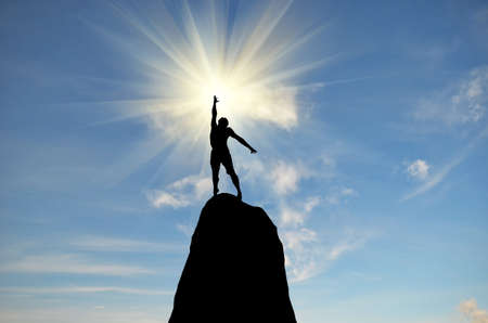 hombre en la cima de la montaña alcanza para el sol