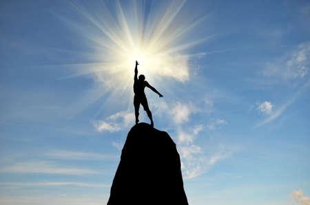 r�sistance: homme sur le dessus de la montagne atteint pour le soleil