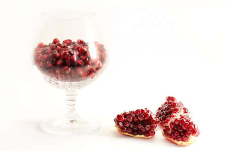 Pomegranate fruit arranged in a glass on a white background photo