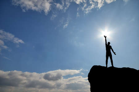 victory: man on top of the mountain reaches for the sun