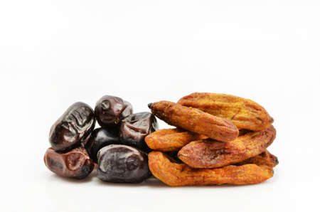 imposed: imposed by a bunch of dates and dried bananas on white background