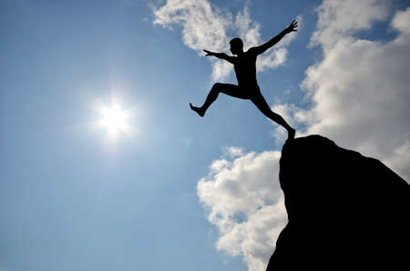 cliff jumping: silhouette of a man jumping off a cliff in the direction of the bright sun