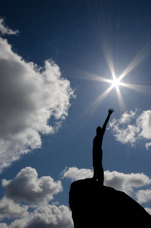 mountaineering: man on top of the mountain reaches for the sun
