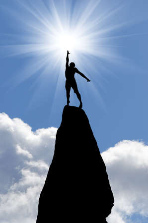 man on top of the mountain reaches for the sun Stock Photo - 12984419