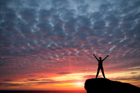 winning woman: silhouette of a girl standing on a cliff side in his arms against the sunset