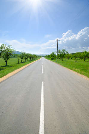 infinity road: asphalt road runs along with the markings of green meadows Stock Photo