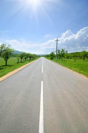 autobahn: asphalt road runs along with the markings of green meadows Stock Photo