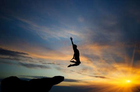 climber: mensen springen van de top van de berg op de achtergrond van de zonsondergang