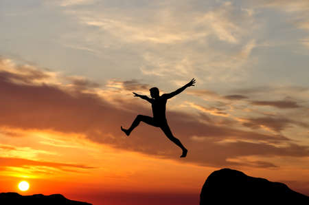cliff top: silhouette of a man jumping off a cliff in the direction of the bright sun