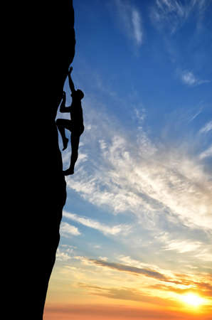 silhouette of a climber conquers the top of a steep hill photo