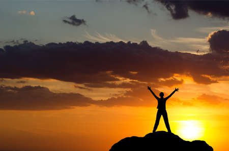 silhouette of a girl standing on a cliff side in his arms against the sunset