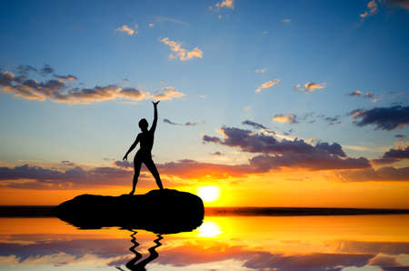 silhouette of a girl standing on a cliff side in his arms against the sunset photo