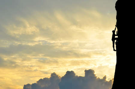 mountaineering: silhouette of a climber conquers the top of a steep hill