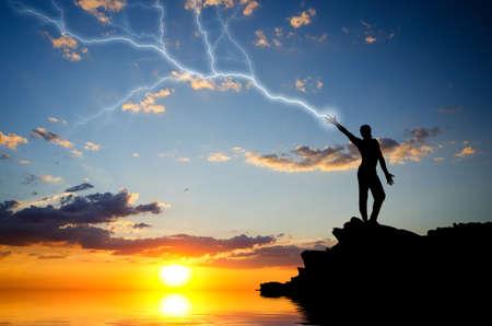 rayo electrico: silueta de un hombre en la cima de una montaña fabricantes de cremallera mano. composición natural Foto de archivo