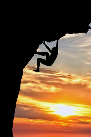 silhouette of a person without protection climbs the rock in the background of the sunset