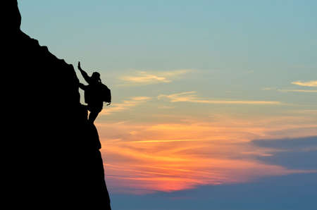 silhouette of a person without insurance climbs the rock in the background of the sunset Stock Photo - 16567608