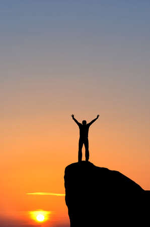 glädje: mannen på toppen av berget sträcker sig efter solen