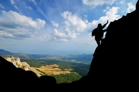 conquers: Silhouette climber conquers mountain peak