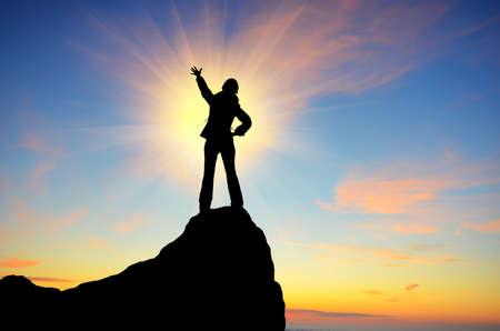 mountain climber: silhouette di una ragazza in piedi su una scogliera tra le braccia contro il tramonto