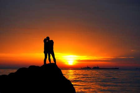 일몰의 배경에 언덕 바다 해안에 서있는 실루엣 남자와 여자
