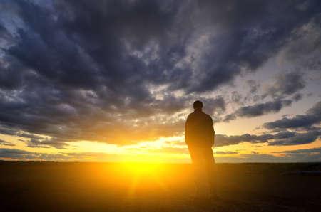 석양에 남자의 실루엣입니다. 감정적 인 장면.