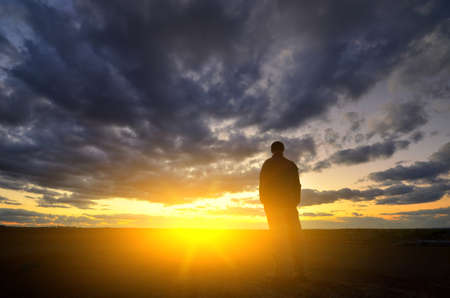 Silhouette of man at the sunset. Emotional scene.