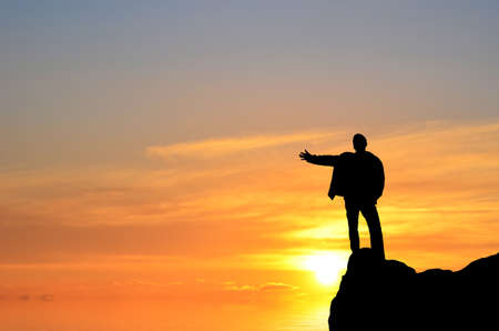 man on top of the mountain reaches for the sun photo