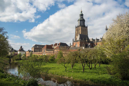 Walburgiskerk and city walls in Zupthen, Holland. In the foreground an orchard full of blooming fruit trees.