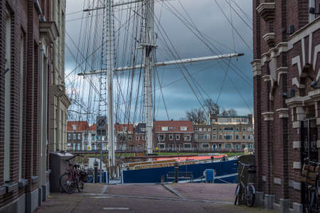 Sailing ship Admiraal van Kinsbergen moored at the IJsselkade in Kampen, Netherlands, seen from the Marktgang, under a gray and cloudy sky.