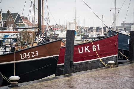 Old smacks in the harbor of Urk on a misty and rainy winter day. Editorial