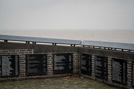 Monument at Urk for fishermen at sea, with black marble plaques with years, names and ages. In the background a foggy IJsselmeer with a ship on the horizon.