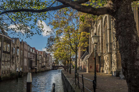Voorstraatshaven and Grote Kerk in Dordrecht, Netherlands on a sunny afternoon. The trees have autumn colors and the sky is blue with clouds.