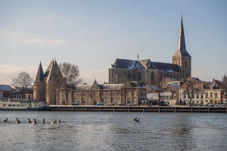 Bovenkerk and Koornmarkt gate in Kampen on a cold winter morning with some snow. In the foreground the IJssel river.