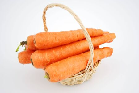 A basketfull of carrots isolated on white background.