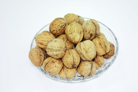 A dish with walnuts isolated on white background.