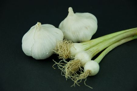 Onions and garlic isolated on dark gray background.