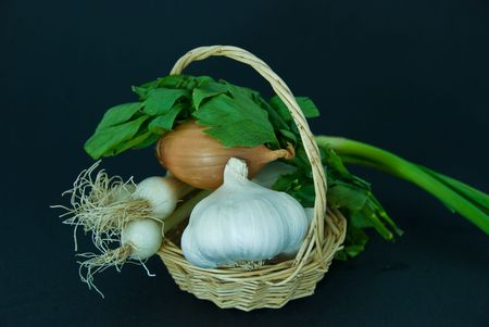 Onions, garlic and loveage isolated on dark gray background. Stock Photo