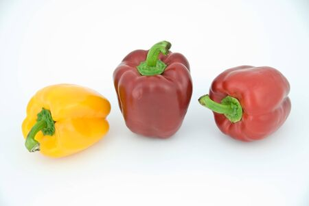 Two red and one yellow paprika isolated on white.