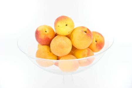 Some apricots meet them in a glass dish. Isolated on white. Stock Photo