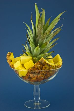 Pineapple branch and slices in a glass dish.