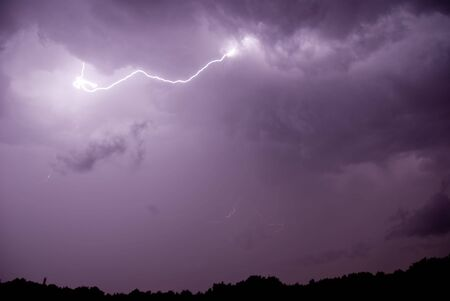 A lightning with stormy clouds and some rain. Stock Photo