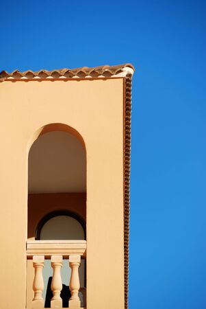 A part of a building in the sunlight in spain with clear blue sky.
