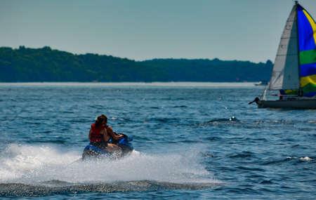 Women on jet ski approaching a sailboat